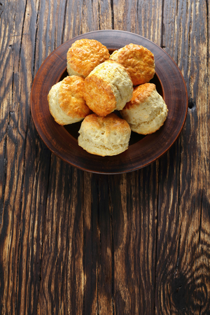 delicious freshly baked homemade english scones on clay plate on wooden table,  vertical view from above