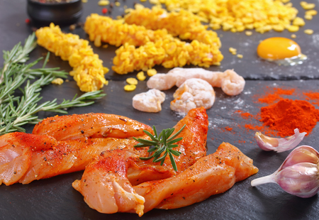 raw chicken breast strips on black stone plate with corn flakes, egg yolk, rosemary and spices, view from above, close-up Фото со стока