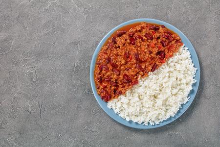 hot delicious chili con carne with whole red kidney beans on plate with boiled rice on concrete table, classic recipe, view from above