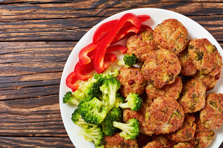 baked in oven juicy meat broccoli meatballs stuffed with grated cheese on white plate on old wooden table, healthy low calories recipe, view from above, close-up Stock Photo