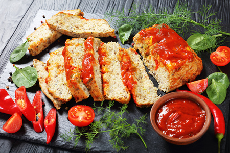 delicious sliced fish terrine with pepper, fresh greens and tomato sauce on black slate cutting board on dark wooden table, view from above, close-up Imagens