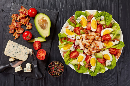 delicious american cobb salad of hard boiled egg, blue mold cheese, crispy fried bacon, romaine lettuce, grilled chicken breast, tomato and avocado chunks on a plate. ingredients on table