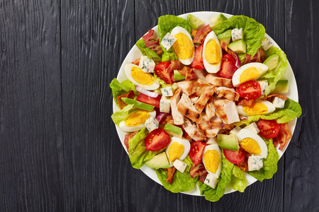 delicious american cobb salad of hard boiled egg, blue mold cheese, crispy fried bacon, romaine lettuce, grilled chicken breast, tomato and avocado chunks on a plate,view from above, flat lay