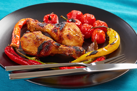 portion of delicious grilled chicken drumsticks with chili peppers and cherry tomatoes served on a black plate with silver fork and knife, horizontal view from above, close-up Stock Photo