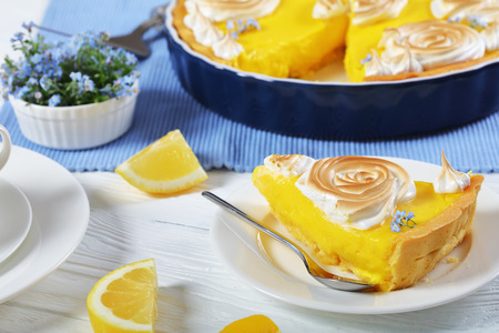 piece of Classic french lemon tart or Tarte au citron on a plate and in a baking dish with a smooth lemon filling decorated with meringue roses and edible fresh flowers, close-up 版權商用圖片 - 101373334