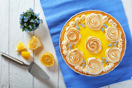 Classic lemon tart -  crisp pastry with a smooth lemon filling decorated with meringue roses and edible fresh flowers. bouquet of forget-me-not and cake spatula at background, view from above