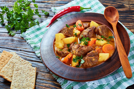 beef stew with vegetables or estofado de carne in a clay bowl on a wooden table, spain cuisine, view from above, close-up