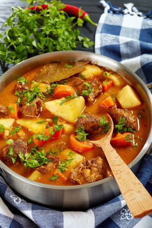 beef stew with vegetables in a spicy gravy or estofado de carne in a metal casserole on a wooden table, authentic recipe, vertical view from above, close-u Imagens