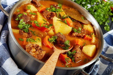 stewed beef with vegetables in a spicy gravy or estofado de carne in a metal casserole with wooden spoon, authentic recipe, view from above, close-up