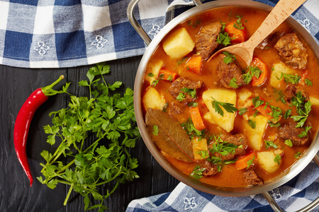 stewed beef with potato, carrots in a spicy gravy or estofado de carne in a metal casserole with wooden spoon, authentic recipe, view from above, close-up