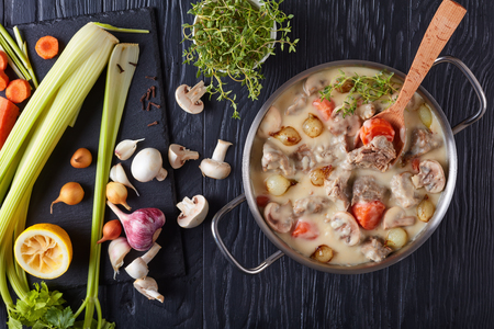 creamy veal stew or blanquette de veau - pieces of veal stewed with mushrooms, glazed pearl onions, herbs and vegetables in a casserole on black wooden table, ingredients on slate board, close-up
