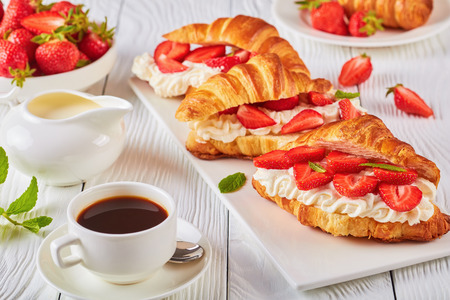 summer breakfast - croissant sandwiches with fresh ripe strawberries and whipped cream cheese on a platter. cup of coffee, jug of fresh cream and bowl with strawberries on white wooden table, close-up