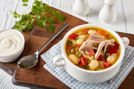 delicious pork vegetable soup with white beans, green peas, red bell pepper, herbs, species in a white bowl with silver spoon and sour cream on a wooden board, close-up
