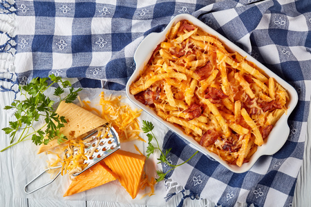 aussie fries smothered in melted cheese and bacon in a baking dish on a white wooden table with ingredients at the background, view from above, flat lay Stockfoto