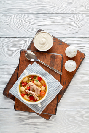 delicious pork vegetable soup with white beans, green peas, red bell pepper, herbs, species in a white bowl with silver spoon and sour cream on a wooden board, vertical view from above Stock Photo