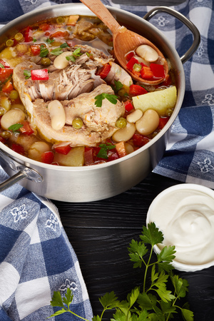 delicious thick pork vegetable soup with white beans, green peas, red bell pepper, herbs, species in a metal casserole with wooden spoon, on a black wooden table, view from above