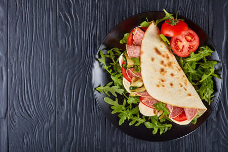 italian piadina with mozzarella, tomato, salami slices, grilled zucchini and arugula on a black plate on a black wooden table, view from above, flat lay Archivio Fotografico
