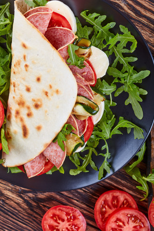 open sandwich - italian piadina with mozzarella, tomato, salami slices, grilled zucchini and arugula on a black plate with ingredients on a cutting board, vertical view from above, close-up Stock Photo