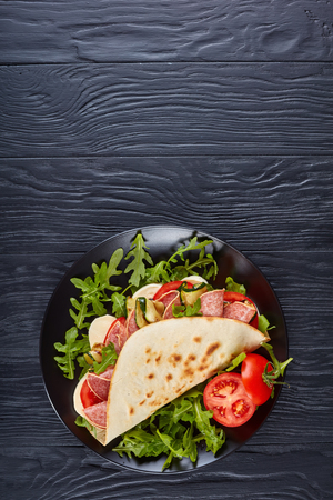 freshly baked italian piadina with mozzarella, tomato, salami slices, grilled zucchini and arugula on a black slate plate on a black wooden table, vertical view from above, flat lay