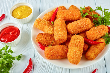 spanish deep-fried golden brown potato croquettes, croquetas on a white plate with chili peppers, mustard and tomato sauce on a wooden table, view from above, close-up Zdjęcie Seryjne
