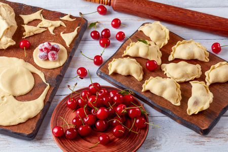uncooked cherry dumplings on a wooden cutting board with dough, rolling pin and plate with fresh cherries at the background, close-up Banco de Imagens - 103512695
