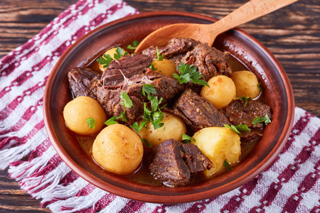 hot Beef Stew with tender cubes of meat, whole new potatoes, onion and herbs in a clay bowl on old rustic wooden table with napkin, irish cuisine, horizontal view from above, close-up