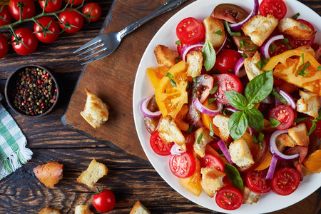 delicious fresh classic italian salad panzanella with tomatoes, croutons basil and onion rings on a white plate on an old wooden table with ingredients, view from above, flat lay, close-up