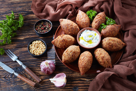 deep fried kibbeh of ground beef meat mixed with bulgur, stuffed with fried minced meat with pine nuts, spices, garlic and herbs on a clay plate on an old dark wooden table, view from above 写真素材 - 104764839