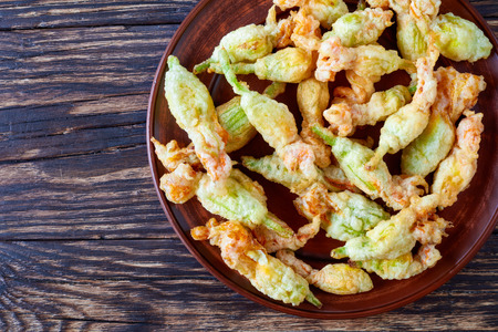fresh zucchini flowers was stuffed with ricotta, parmesan, anchovies and deep fried in tempura batter, italian cuisine, horizontal view from above, close-up, flat lay