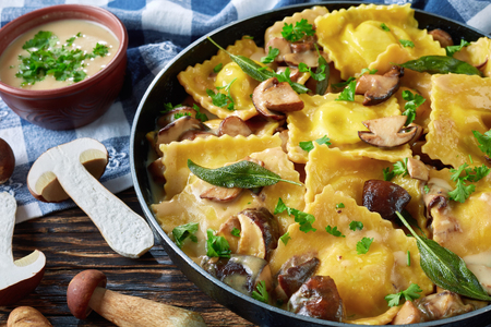 hausgemachte Ravioli gefüllt mit Ricotta-Käse, gekocht in cremiger Knoblauchpilzsauce in einer Pfanne, Nahaufnahme Standard-Bild