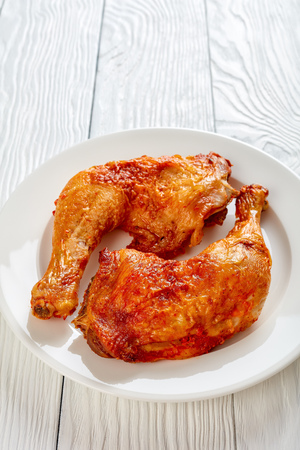 crispy fried chicken legs on a white plate on a wooden table, flat lay, close-up,vertical view from above Banque d'images