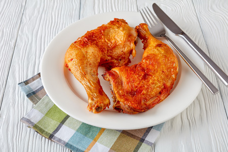 close-up of delicious juicy fried chicken legs with golden skin crust served on a white plate with fork and knife on a wooden table, horizontal view from above