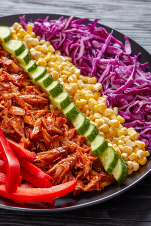 Slow cooker pulled pork rancho salad with arranged rows of thinly sliced red cabbage, corn, sweet pepper, cucumber and chopped jalapeno on a black plate on a wooden table, vertical view from above