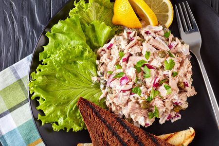 close-up of Tuna, capers and red onion salad served with toasted bread, lemon wedges and lettuce leaves on a black plate on a wooden table with napkin, view from above, flat lay