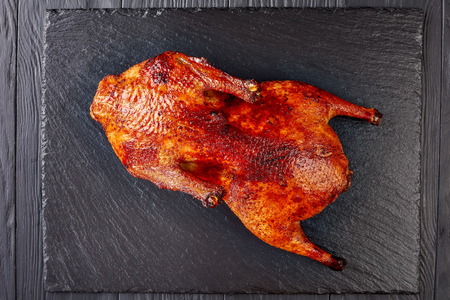 whole grilled duck with extremely crispy skin on a black slate tray for Thanksgiving or Christmas Dinner, view from above, flat lay, close-up