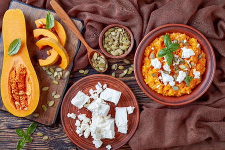 creamy butternut pumpkin and feta Mash with rice sprinkled with pumpkin seeds,  basil leaves on a  earthenware plate with ingredients on a wooden rustic table, view from above, flat lay