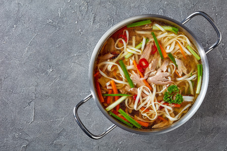 overhead view of poultry noodle vegetables soup in a metal casserole on a concrete table, view from above, flatlay