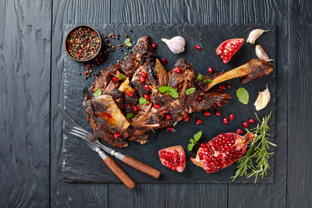 overhead view of delicious roast leg of lamb served with pomegranate seeds, mint leaves, spices and rosemary on a black slate plate on a wooden table,view from above, flat lay Фото со стока
