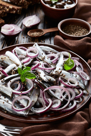 salted sprats marinated with red onion rings on an earthenware plate  coriander seeds, brown cloth, fork and knife on an old rustic wooden table, vertical view from above, close-up