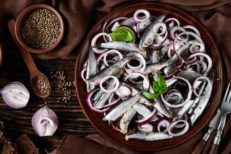 salted sprats marinated with red onion rings on an earthenware plate. coriander seeds, brown cloth, fork and knife on an old rustic wooden table, view from above, close-up, flatlay