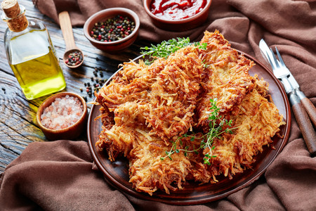 delicious grated potato coated and deep fried pork chops on a clay plate on a rustic wooden table with brown cloth, peppercorns, tomato sauce in a bowl, view from above, close-up