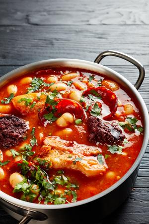 Ragoût de haricots avec chorizo, bacon et boudins dans une casserole en métal sur une table en bois noir avec des ingrédients sur une planche à découper, cuisine espagnole, vue verticale d'en haut