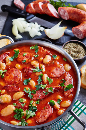hearty beans stew with sausages, herbs and spices in tomato sauce in a metal casserole on a concrete table with ingredients, fasolka po bretonsku, comfort food, vertical view from above Stock fotó
