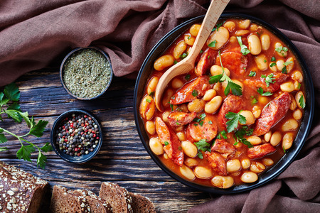 overhead view of hearty beans stew with sausages, herbs and spices in tomato sauce in a black bowl with spoon, on a rustic wooden table, fasolka po bretonsku, polish cuisine, view from above, flatllay