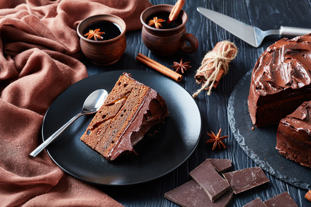 portion of chocolate Cake with apricot jam filling topped with Chocolate Ganache served on a black plate with mulled wine in clay rustic cups on a black wooden table, view from above, close-up Banco de Imagens