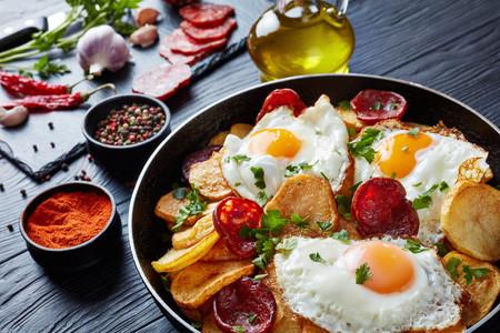 délicieux œufs frits au plat avec pommes de terre, saucisses de porc émincées dans une poêle sur une table en bois noir avec des ingrédients à l'arrière-plan, vue horizontale d'en haut, gros plan