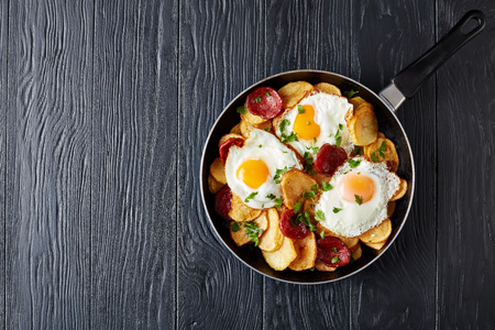 delicious fried sunny side up eggs with potatoes, thinly sliced pork sausages in a skillet on a black wooden table, european cuisine, spain huevos rotos, view from above, flatlay, copy space Foto de archivo