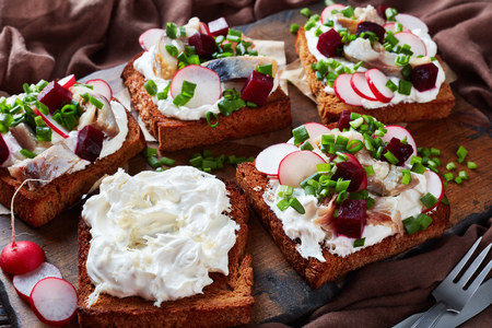 Smorrebrod - danish open faced sandwiches with smoked mackerel slices, cream mixed with shredded horseradish, beetroot, fresh radish, onion on a dark cutting board Imagens