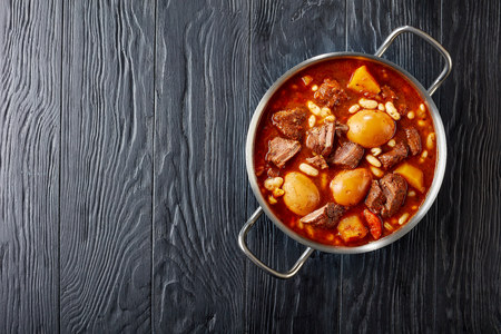 Traditional Jewish Cholent or Hamin - main dish for the Shabbat meal slow cooked beef with potato, beans and brown eggs in a metal casserole on a black wooden table, view from above, copy space