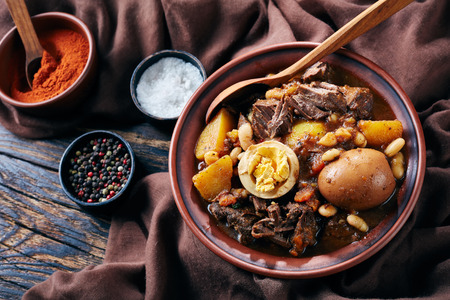 close-up of Traditional Jewish Cholent Hamin - main dish for the Shabbat meal, slow cooked beef with potato, beans and brown eggs in a bowl on a rustic wooden table, view from above Stock fotó